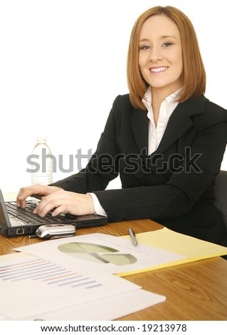 portrait of young business woman, typing on laptop and looking at camera