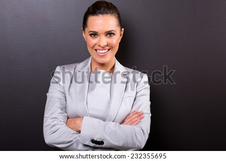 portrait of young business woman with arms folded on black background - stock photo