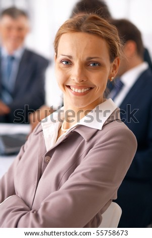 Portrait of young business woman with folded hands in front of her colleagues.