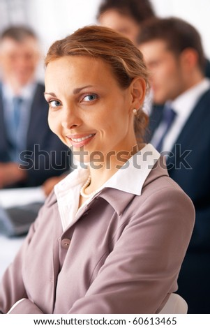 Portrait of young business woman with folded hands in front of her colleagues. - stock photo