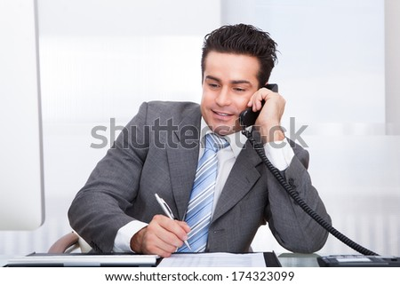Portrait Of Young Businessman At Desk Talking On Telephone - stock photo