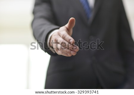 Portrait of young businessman executives extending hands to shake,close-up