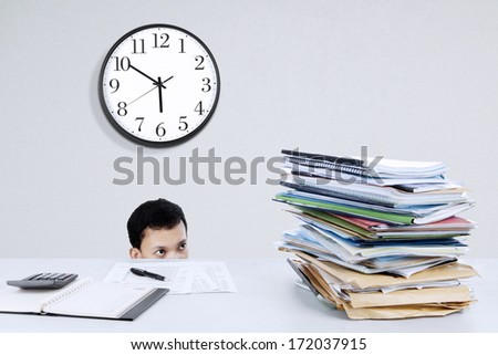 Portrait of young businessman hiding from his job - stock photo