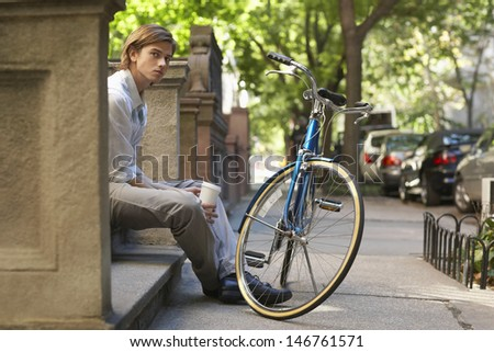 Portrait of young businessman holding disposable coffee cup while sitting on steps in front of bicycle - stock photo