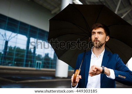 Portrait of  young  businessman holding  umbrella and looking on watch waiting