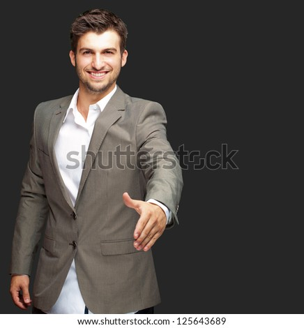 Portrait Of  Young Businessman In A Suit Holds Out His Hand For A Handshake On Black Background - stock photo