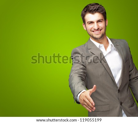 Portrait Of Young Businessman In A Suit Holds Out His Hand For A Handshake On Green Background - stock photo