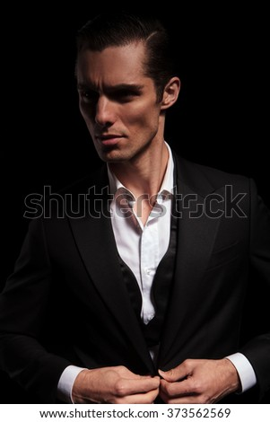 portrait of young businessman in black suit posing in dark studio background closing his jacket and looking away - stock photo