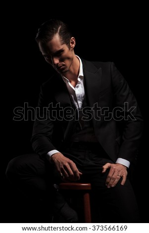 portrait of young businessman in black suit seated in dark studio background looking down