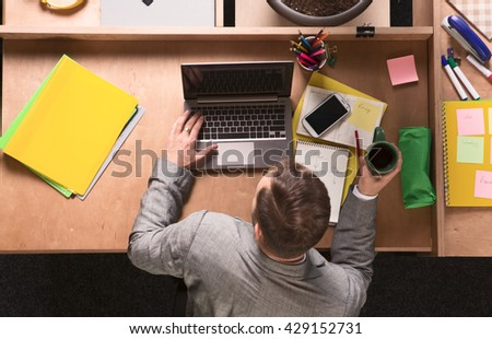 Portrait of young businessman in grey business suit working on laptop computer in office. Man drinking coffee and looking at screen. - stock photo