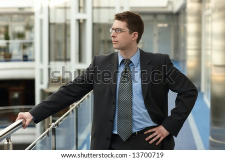 Portrait of young businessman in modern business office building corridor