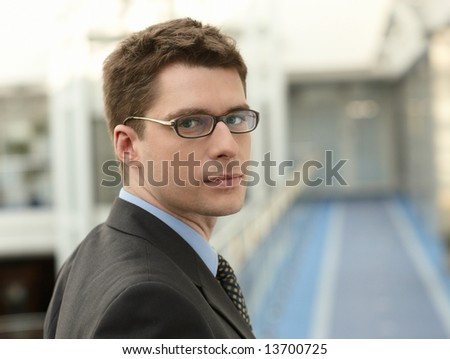 Portrait of young businessman in modern business office building corridor - stock photo