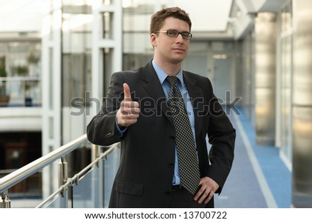 Portrait of young businessman in modern business office building corridor showing OK success thumbs up sign