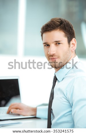 Portrait of young businessman in office with big window. Businessman using laptop and looking at camera