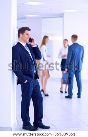 Portrait of young businessman in office with colleagues in the background and using mobile - stock photo