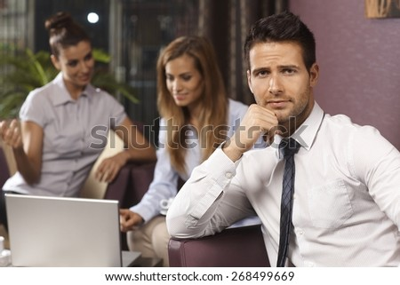 Portrait of young businessman in trouble, colleagues working at background. - stock photo