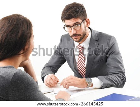 Portrait of young businessman interviewing young business woman, while sitting at desk at office. Business people.  - stock photo