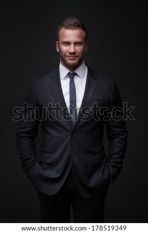 Portrait of young businessman isolated on dark background - stock photo