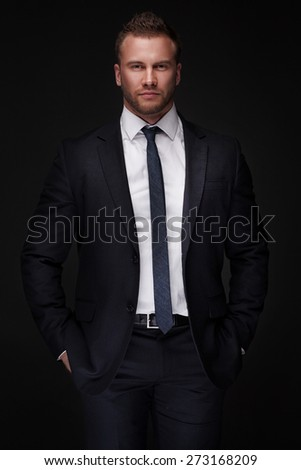 Portrait of young businessman isolated on dark background blending into the background