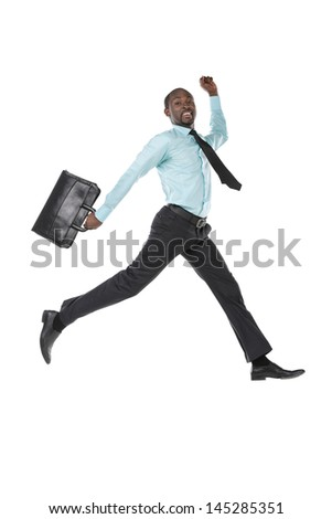Portrait of young businessman jumping in air with briefcase - stock photo