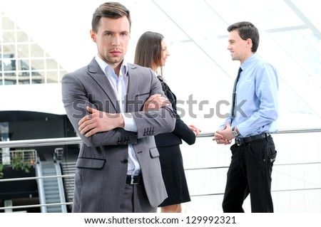 Portrait of young businessman looking at camera in working environment