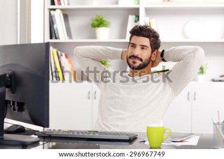 Portrait of young businessman relaxing at office. Creative designer sitting at workplace in front of computer and leans back in his chair while relaxing. - stock photo