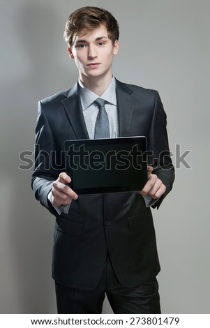 Portrait of young businessman showing touch screen computer, on gray background - stock photo