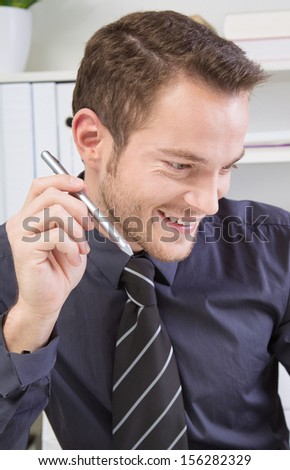 Portrait of young businessman smiling and working in office
