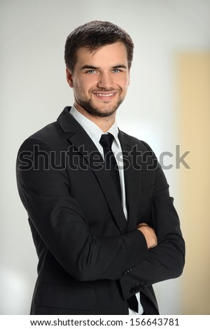 Portrait of young businessman smiling inside office building