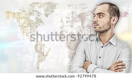 Portrait of young businessman. Standing against world map with photo of people. International business communications concept - stock photo