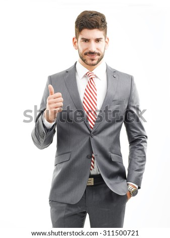 Portrait of young businessman standing and looking at camera while showing thumbs up. Isolated on white background.  - stock photo