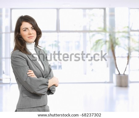 Portrait of young businessman standing in office hall with arms crossed, smiling. ? - stock photo