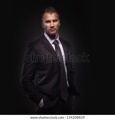 Portrait of young businessman standing with his hands in the pockets, isolated on dark background - stock photo