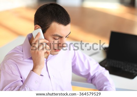 Portrait of young businessman talking on cell phone in office - stock photo