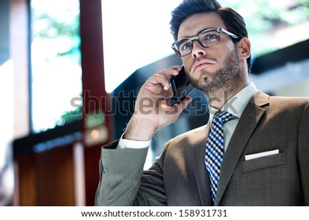 Portrait of young businessman talking  with smartphone - stock photo