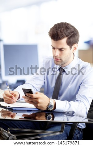 Portrait of  young businessman text messaging on cellphone in office