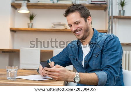 Portrait of young businessman text messaging on mobile phone in office