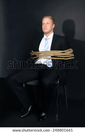 Portrait Of Young Businessman Tied With Rope To A Chair - stock photo