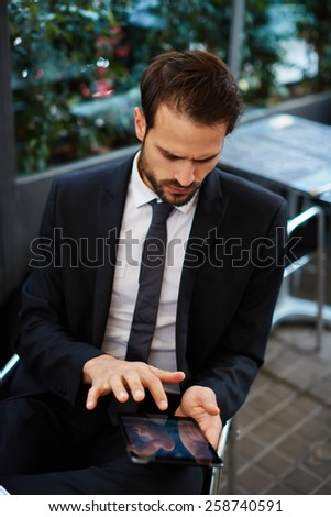 Portrait of young businessman touching digital tablet screen sitting in coffee shop, attractive smart man use tablet pc browsing in internet - stock photo