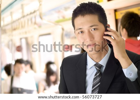 Portrait of young businessman use cellphone in train. - stock photo