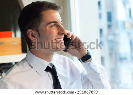 Portrait of young businessman using his mobile phone in office. - stock photo