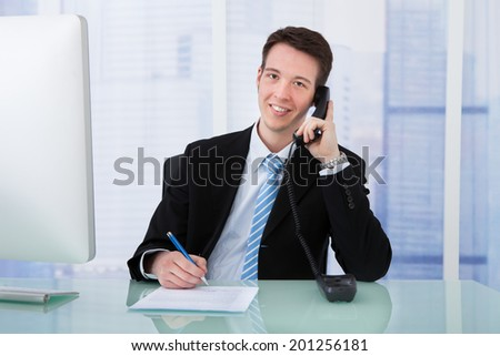 Portrait of young businessman using telephone while writing on document at office desk