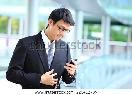Portrait of young businessman wearing glasses and using smartphone. - stock photo