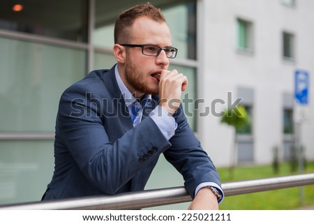 Portrait of young businessman with beard standing in front of office block. He is eating candy bar. Outdoor photo. - stock photo