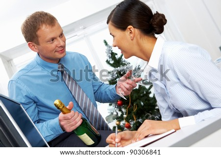 Portrait of young businessman with bottle of champagne and two flutes offering his colleague to drink for New Year - stock photo