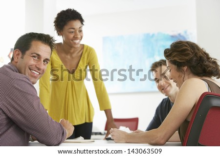 Portrait of young businessman with colleagues in meeting room - stock photo