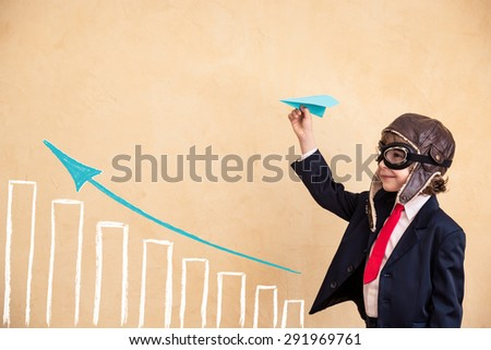 Portrait of young businessman with paper airplane. Success, creative and start up concept. Copy space for your text - stock photo
