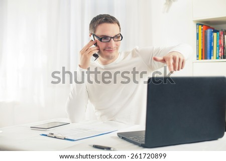Portrait of young businessman working at home using computer and mobile phone.