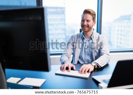 Portrait of young businessman working on computer