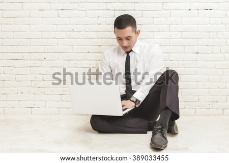 portrait of young businessman working on laptop while sitting on the floor with white brick wall background